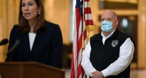 Maryland Gov. Larry Hogan, right, wears a mask as he listens to Maryland Labor Secretary Tiffany Robinson, left, speak during a news conference in Annapolis, Md., Friday, April 10, 2020. Hogan provided several updates on the state's response to the coronavirus pandemic, including key budget actions and efforts to bolster the process to apply for unemployment. (AP Photo/Susan Walsh)