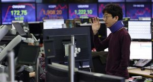 A currency trader gestures at the foreign exchange dealing room of the KEB Hana Bank headquarters in Seoul, South Korea, Friday, April 17, 2020. Shares have advanced in Asia after China's economic growth data, while bleak, was better than expected. (AP Photo/Ahn Young-joon)