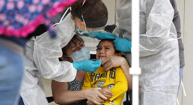 Angel Landaverde, 4, is restrained by his aunt Vilma Landaverde, center left, and medical workers as a swab is placed in his nose during a coronavirus testing at a walk-up testing site, Monday, April 20, 2020, in Annapolis, Md. (AP Photo/Julio Cortez)