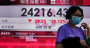 A woman wearing face mask walks past a bank electronic board showing the Hong Kong share index in Hong Kong, Wednesday, May 13, 2020.  Shares fell in Asia on Wednesday after Wall Street logged its biggest loss since the start of the month on worries about the downside of reopening the economy too soon. (AP Photo/Vincent Yu)