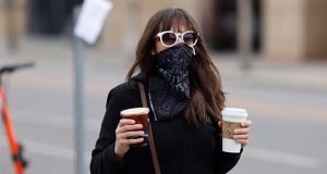 In this May 13, 2020 photo, a pedestrian wears a face mask while carrying drinks from a nearby coffee shop along Larimer Street as businesses slowly re-open with the easing of restrictions to check the spread of the new coronavirus Wednesday in Denver. (AP Photo/David Zalubowski)