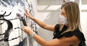 In this Wednesday, May 13, 2020, photo, Amy Witt, owner of the Velvet Window, steam-sanitizes clothes that had been tried on by customers, in Dallas. Small businesses are navigating a new way to work with customers amid concerns of the spread of the coronavirus. (AP Photo/LM Otero)