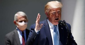 President Donald Trump speaks about the coronavirus in the Rose Garden of the White House, Friday, May 15, 2020, in Washington. Director of the National Institute of Allergy and Infectious Diseases Dr. Anthony Fauci listens at left. (AP Photo/Alex Brandon)
