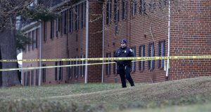 A police officer stands inside a crime scene outside an apartment complex while working the scene of a shooting, Wednesday, Feb. 12, 2020, in Baltimore. Two law enforcement officers with a fugitive task force were injured and a suspect died in the shooting, the U.S. Marshals Service said. (AP Photo/Julio Cortez)