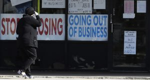 A woman looks at signs at a store in Niles, Ill., Wednesday, May 13, 2020.(AP Photo/Nam Y. Huh)