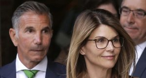 FILE - In this April 3, 2019, file photo, actress Lori Loughlin, front, and her husband, clothing designer Mossimo Giannulli, left, depart federal court in Boston after a hearing in a nationwide college admissions bribery scandal. On Thursday, May 21, 2020, the U.S. Attorney's Office in Boston said Loughlin and Giannulli have agreed to plead guilty to charges of trying to secure the fraudulent admission of their two children to the University of Southern California as purported athletic recruits. (AP Photo/Steven Senne, File)