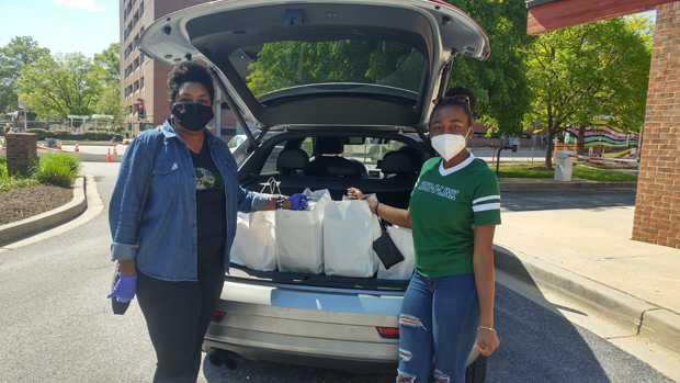 Tawana Thomas-Johnson, left, vice president of diversity and inclusion, with the American Cancer Society, and Tyler Johnson get ready to deliver meals to University of Maryland Medical Center staff members. (Photo by Vivienne Stearns-Elliott)