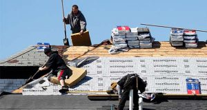 FILE - In this April 2, 2020 file photo, roofers work on removing and placing new shingles in Warren, Mich.  U.S. home-building activity collapsed in March as the coronavirus spread, with housing starts tumbling 22.3% from a month ago. The Commerce Department said Thursday, April 16,  that ground breakings occurred last month at a seasonally adjusted annual rate of 1.2 million units, down from a 1.56 million pace in February.  (AP Photo/Paul Sancya, File)