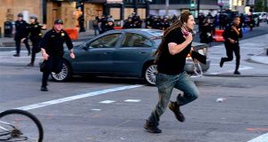 A man runs from police officers in Oakland, Calif., Monday, June 1, 2020. (AP Photo/Noah Berger)