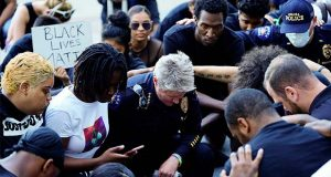 Protesters and police, including Chief Vanessa Wilson, center, kneel together for eight minutes and 46 seconds during a peaceful protest against police brutality, following the death of George Floyd, Tuesday, June 2, 2020, in Aurora, Colo. Floyd died in police custody on Memorial Day in Minneapolis.(Philip B. Poston/The Aurora Sentinel via AP)