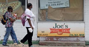Two women walks past a closed down pizza deli, Thursday, June 4, 2020, in Cleveland. The state says more than 34,000 Ohioans filed unemployment claims during the last week of May. That is the lowest figure since Ohio's stay-at-home orders depressed the economy and led to widespread layoffs. The figure released Thursday by the Ohio Department of Job and Family Services is down from about 46,000 claims filed the previous week. (AP Photo/Tony Dejak)