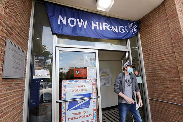 FILE - In this June 4, 2020 photo, a customer walks out of a U.S. Post Office branch and under a banner advertising a job opening, in Seattle. The U.S. government is set to issue its latest report Thursday, June 11, on the layoffs that have left millions unemployed but that have markedly slowed as many businesses have partially reopened and rehired some laid-off workers. (AP Photo/Elaine Thompson, File)