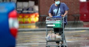 """A shopper wears a mask as she pushes her grocery cart in the rain Thursday, June 25, 2020, in Houston. Texas Gov. Greg Abbott said Wednesday that the state is facing a """"massive outbreak"""" in the coronavirus pandemic and that some new local restrictions may be needed to protect hospital space for new patients. (AP Photo/David J. Phillip)"""