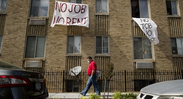"FILE - In this May 20, 2020, file photo, signs that read ""No Job No Rent"" hang from the windows of an apartment building during the coronavirus pandemic in Northwest Washington. The pandemic has shut housing courts and prompted authorities around the U.S. to initiate policies protecting renters from eviction. But not everyone is covered, and some landlords are turning to threats and harassment to force tenants out. (AP Photo/Andrew Harnik, File)"