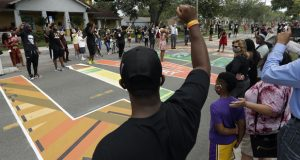 People raise their arms in solidarity as Sierra Davis Sanders and Ericka Still perform during a Juneteenth 2020 celebration outside the Dr. Carter G. Woodson African American Museum Friday, June 19, 2020, in St. Petersburg, Fla. Juneteenth marks the day in 1865 when federal troops arrived in Galveston, Texas to take control of the state and ensure all enslaved people be freed. (AP Photo/Chris O'Meara)