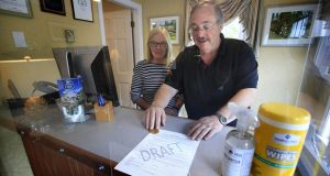 """Cod Cove Inn owners Ted and Jill Hugger show a draft of a compliance form that inn owners may be required to have out-of-state guests sign before being allowed to check in at their inn in Edgecomb, Maine. The form is part of the """"Keep Maine Healthy"""" plan the state is proposing to help prevent the spread of the coronavirus. Residents of New Hampshire and Vermont would be exempt. (AP Photo/Robert F. Bukaty)"""