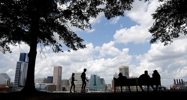 The Baltimore skyline is seen at a distance as people enjoy a warm day, Wednesday, July 1, 2020, in the Federal Hill neighborhood of Baltimore. (AP Photo/Julio Cortez)