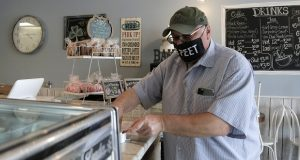 Mike Novak, right, pays for items while while wearing a mask with a message requesting others to stay away more than six feet while shopping in a bakery, in Nottingham earlier this year. (AP Photo/Julio Cortez)