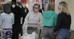People wear masks to protect themselves and others from the coronavirus as they shop at the Pennsylvania Dutch Market in Cockeysville earlier this year. (AP Photo/Julio Cortez)