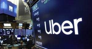 FILE - In this May 30, 2019, file photo the logo for Uber appears above a trading post on the floor of the New York Stock Exchange. Less than a month since its disappointing stock market debut, Uber said Tuesday, June 4, that the IRS is reviewing its 2013 and 2014 taxes. (AP Photo/Richard Drew, File)