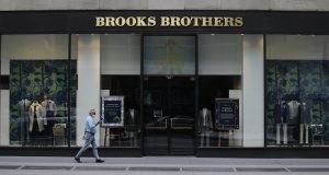 Pedestrians wearing protective masks walk past a Brooks Brothers location on July 8, 2020, in New York. A retail venture owned by licensing company Authentic Brands Group and mall owner Simon Property Group has bought Brooks Brothers.  (AP Photo/Frank Franklin II, File)