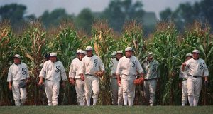 """FILE - In this June 22, 1997, file photo, Ghost Players emerge from the cornfield at the """"Field of Dreams"""" movie site in Dyersville, Iowa. The owners of the movie site have put the field up for sale. The asking price is $5.4 million for the baseball diamond, a two bedroom house, six outbuildings, and a 193-acre parcel of land. (AP Photo/Charlie Neibergall, File)"""
