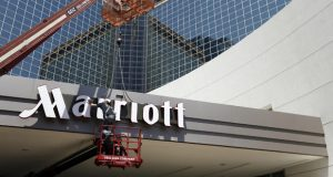 A man works in 2013 on a new Marriott sign in front of the former Peabody Hotel in Little Rock, Ark.  (AP Photo/Danny Johnston, File)