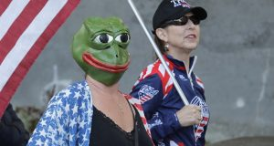 """A woman wears a mask of Pepe the Frog, a cartoon figure appropriated by far-right groups, as she stands next to a woman holding a U.S. flag and a """"Trump 2020"""" hat, Thursday, May 14, 2020, during a protest rally at the Capitol in Olympia, Wash. The demonstration was against Washington Gov. Inslee and Washington state's stay-at-home orders restricting some businesses and public gatherings in efforts to prevent the spread of the coronavirus. (AP Photo/Ted S. Warren)"""