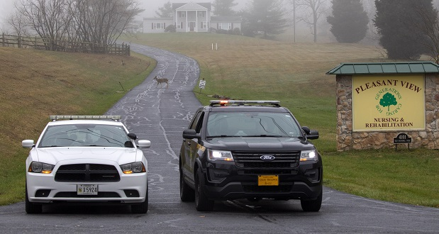 A Carroll County sheriff officer and a Maryland state trooper guard the driveway to the Pleasant View Nursing Home, in Mount Airy on March 29. The nursing home was the first in Maryland to experience a major outbreak of COVID-19. (AP File Photo/Jacquelyn Martin)