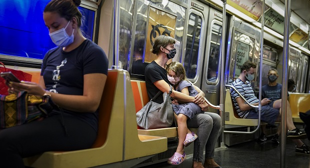 FILE - In this Aug. 17, 2020, file photo, a child rests on a subway car while riders wear protective masks due to COVID-19 concerns in New York. The number of Americans newly diagnosed with the coronavirus is falling — a development experts credit at least partly to increased wearing of masks — even as the outbreak continues to claim nearly 1,000 lives in the U.S. each day. (AP Photo/John Minchillo, File)