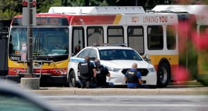 Authorities shield behind a police car near a public transportation bus, Friday, Aug. 14, 2020, in Lutherville, Md., North of Baltimore. Per a twitter feed from the Baltimore Police, they are asking motorists to avoid the area. (AP Photo/Julio Cortez)