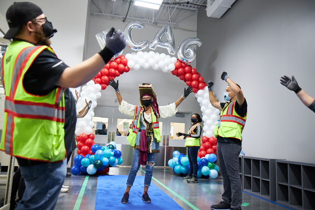 Lisa Hafer passes under a balloon as Amazon associates celebrate the first day of work at the new Amazon Fulfillment Center at Tradepoint Atlantic. (Photo by Brian O'Doherty, O'Doherty Photo)