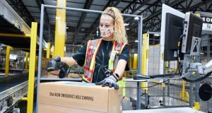 Amazon employee Mira Beh gets a box of waterproof socks ready for shipment at the Amazon Fulfillment Center at Tradepoint Atlantic. It was the first order shipped from the new fulfillment center. (Photo by Brian O'Doherty, O'Doherty Photo)