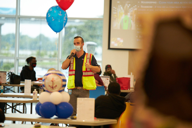 Amazon site leader Jake Williams addresses the crowd of associates on the first day of work at the new fulfillment center at Tradepoint Atlantic. (Photo by Brian O'Doherty, O'Doherty Photo)