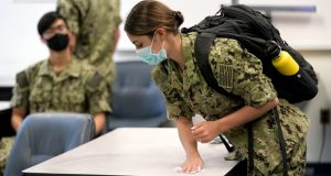 A midshipman uses a sanitizing wipe to clean her desk before the start of a leadership class at the U.S. Naval Academy, Monday, Aug. 24, 2020, in Annapolis, Md. Under the siege of the coronavirus pandemic, classes have begun at the Naval Academy, the Air Force Academy and the U.S. Military Academy at West Point. But unlike at many colleges around the country, most students are on campus and many will attend classes in person. (AP Photo/Julio Cortez)