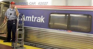 FILE - In this file photo of  Nov. 17, 2005, a skycap stands next to an Amtrak train waiting for passengers a platform in New York's Penn Station. U.S. taxpayers spent about $32 subsidizing the cost of the typical Amtrak passenger in 2008, about four times the rail operator's estimate, according to a new report. (AP Photo/Mary Altaffer, File)