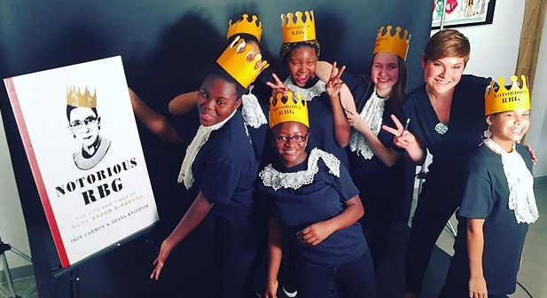 """In this Oct. 29, 2015, photo provided by The Lower Eastside Girls Club, members of the club pose with author Shana Knizhnik, second from right, at a book launch event for """"Notorious RBG: The Life and Times of Ruth Bader Ginsburg,"""" by Irin Carmon and Knizhnik, in New York. Younger women and girls say they were inspired by the late justice's achievements, her intellect and her fierce determination as she pursued her career. (Allana Clarke/The Lower Eastside Girls Club via AP)"""