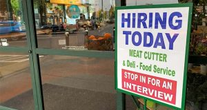 "A sign that reads ""hiring today,"" is shown at a grocery store in Olympia, Wash., advertising a job opportunity for a meat cutter on Saturday, Oct. 3, 2020. The number of Americans seeking unemployment benefits fell slightly last week to a still-high 840,000, evidence that job cuts remain elevated seven months into the pandemic recession. (AP Photo/Ted S. Warren)"