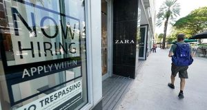 """A pedestrian walks past a Zara store with a large """"Now Hiring,"""" sign in the window, Monday, Oct. 12, 2020, along the famed Lincoln Road area in Miami Beach, Fla.  The number of Americans seeking unemployment benefits rose last week to 898,000, a historically high number that is evidence that layoffs remain a hindrance to the economy's recovery from the pandemic recession that erupted seven months ago.  (AP Photo/Wilfredo Lee)"""
