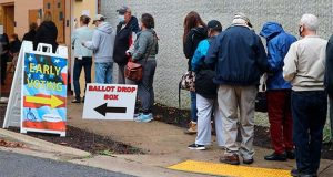 Voters wait in line to enter the Pip Moyer Recreation Center, Monday, Oct. 26, 2020 in Annapolis, Md., on the first day of in-person early voting in the state. (AP Photo/Brian Witte)