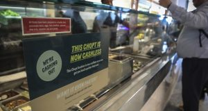 A restaurant sign alerts customers that it's 'now cashless' Thursday, Jan. 23, 2020, in New York City. That status didn't last, as city lawmakers later approved a measure to require stores and restaurants to accept cash. Still, the pandemic has hastened the move by many businesses and consumers away from cash. (AP Photo/Bebeto Matthews)