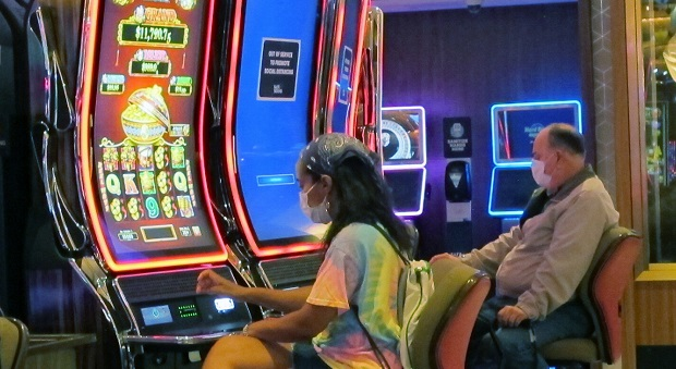 Gamblers wear face masks while playing slot machines at the Hard Rock casino in Atlantic City, New Jersey, on July 2, 2020, the first day it reopened after being closed for four months due to the coronavirus outbreak. (AP Photo/Wayne Parry)