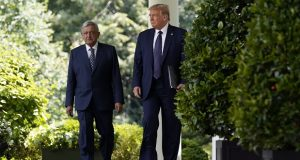 President Donald Trump and Mexican President Andres Manuel Lopez Obrador arrive for a July 8, 2020, event in the Rose Garden at the White House in Washington. The Supreme Court is agreeing to review a Trump administration policy that makes asylum-seekers wait in Mexico for U.S. court hearings. (AP Photo/Evan Vucci)