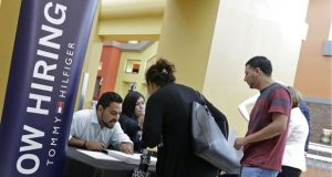 FILE - In this Tuesday, Oct. 3, 2017, file photo, job seekers stand at a booth at a job fair at the Dolphin Mall in Sweetwater, Fla.  U.S. businesses kept hiring at a healthy pace in January 2018, a sign the economy is off to a solid start for the year, a private survey found. Payroll processor ADP says that companies added 234,000 jobs, led by big gains in services firms, such as hotels, restaurants, retail, education and health. (AP Photo/Alan Diaz, File)