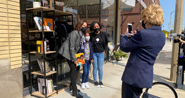 """Michigan Sen. Debbie Stabenow, right, takes a picture of Vice President-elect Kamala Harris posing for a photo on Sept. 22, 2020 with Egypt Otis and her nine-year-old daughter Eva Allen in front of their downtown Flint, Mich., bookstore, the Comma Bookstore & Social Hub. For countless women and girls, Harris' achievement of reaching the second highest office in the country represents hope, validation and the shattering of a proverbial glass ceiling that has kept mostly white men perched at the top tiers of American government. """"My daughter is going to be a part of history because she had the opportunity to have a conversation with our first Black woman vice president,"""" said Otis.  """"It just shows you how important representation is.""""  (AP Photo/Katrease Stafford)"""