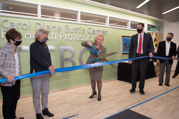 CCBC President Dr. Sandra Kurtinitis, center, cuts the ceremonial ribbon opening the Carol Diane Eustis Center for Health Professions. Joining Kurtinitis in the event were, from left, Eustis' sister Gail Franklin, Eustis' wife Linda Twenty, Baltimore County Executive John Olszewski Jr., and CCBC Foundation chair Michael A. Carper.