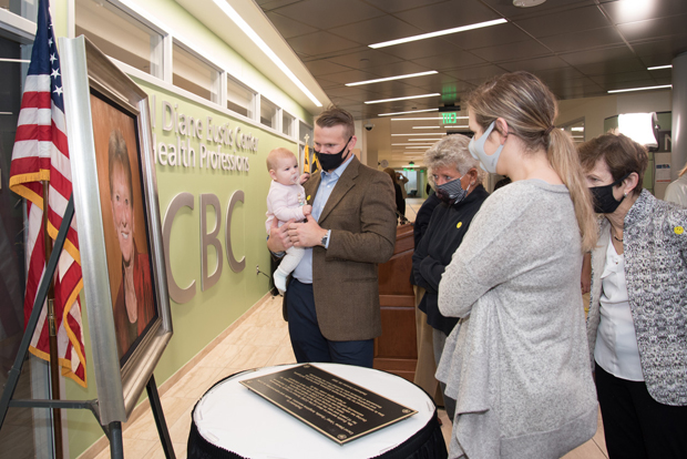 From left, Kyle Franklin, with baby Evelyn Carol, Linda Twenty, Chelsea Franklin and Gail Franklin view the portrait and commemorative plaque of Carol Diane Eustis at the Carol Diane Eustis Center for Health Professions at CCBC Essex that will be prominently displayed in the building.