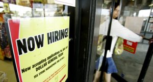 A now hiring sign hangs in the window of a Dollar General store as a customer leaves Thursday, Oct. 19, 2006,  in Houston. The government reported Thursday that new requests for unemployment insurance benefits last week were at their lowest level in nearly three months. Initial jobless claims dropped 10,000 to a seasonally adjusted level of 299,000 in the week ended Oct. 14, the Labor Department said Thursday. (AP Photo/David J. Phillip)