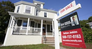 A for sale sign stands in front of a house, Tuesday, Oct. 6, 2020, in Westwood, Mass.   U.S. long-term mortgage rates edged lower this week, reaching record lows for the 14th time this year against the backdrop of the pandemic-ravaged economy. Mortgage finance giant Freddie Mac says on Thursday, Dec. 3,  the average rate on the 30-year fixed-rate home loan slipped to 2.71% from 2.72% last week.  (AP Photo/Steven Senne)