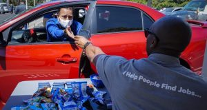 Brandon Earl, right, helps David Lenus, a job seeker, fill out an application at a drive up job fair for Allied Universal on May 6 during the coronavirus pandemic, in Gardena, California. (AP Photo/Chris Carlson, File)